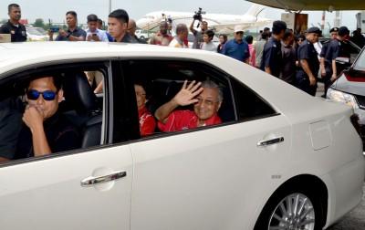 首相敦马在乘车离开机场时向媒体挥手致意。