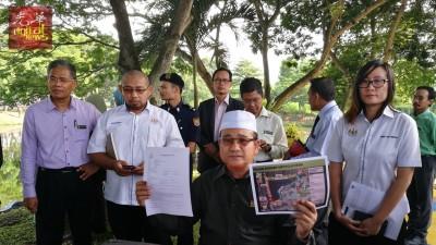 罗查理(坐者)出示报案书及升级改造公园平面图,斥责破坏分子不负责任;右后站者为王育璇。