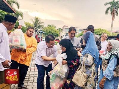 倪可敏在沙鲁奈因及添仁奈都陪同下分发开斋恩物及青包予贫苦家庭。
