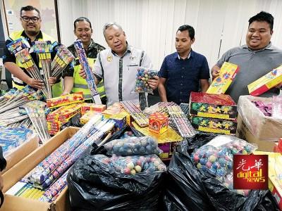 阿都拉迪(中)及执法官员展示总值3万6千令吉的各类走私烟花爆竹。