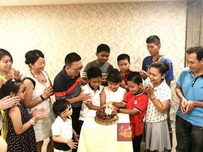 依丽(右2起)、友强、艳芬、友福、李团才与众人为三胞胎庆祝10岁的生日。