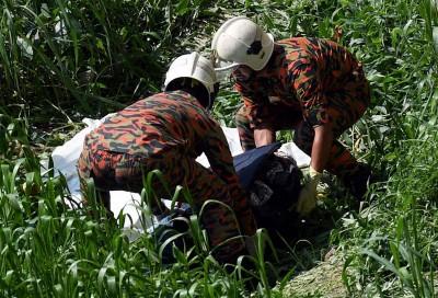 消拯员合力将藏有尸体的行李箱抬上岸。