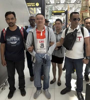嫌犯由8称来自柔州刑事组警员押送回国。(马新社照片)
