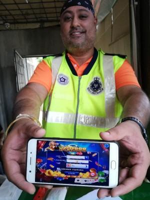 达温警长展示手机使用的非法赌博应用程序。