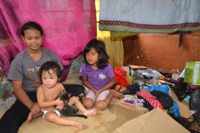 抱着小猫的女童挤坐在屋内有限的空间。