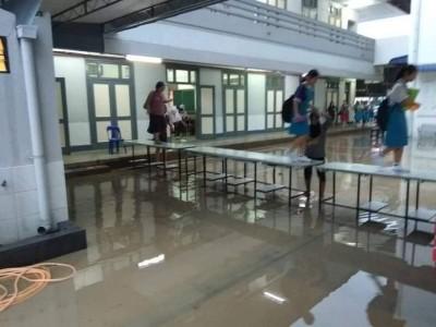 学生走在桌子上避开积水。