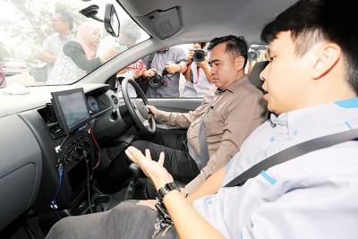 陆兆福聆听有关自动考车系统的操作讲解。