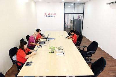 本报职员在吉玻新闻中心新办事处上班。