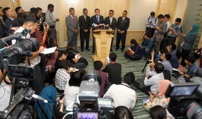 陆兆福(中)由官员陪同,公布电召车管制详情,吸引大批媒体采访。