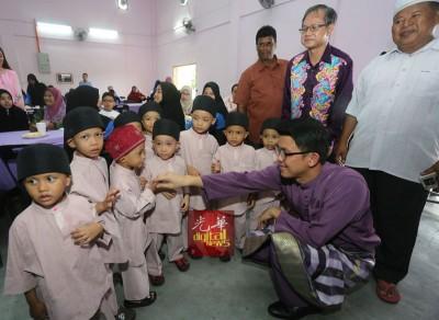 李文材(站者右2) 及陈家兴(右蹲者)向儿童问安。