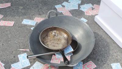 炒锅里的一盘沙石,讽刺商企业者罔顾村民生计,如同在他们饭碗里倒沙。