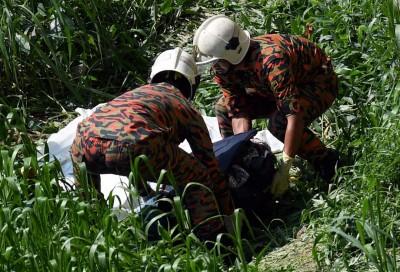 消拯员受召从河岸把装有人体碎尸的袋子拿上来。