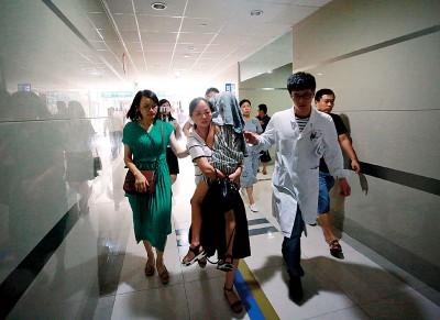 来自浙江海宁的首批6名游客,返抵杭州萧山后,其中一名在船难中获救的小女孩(以毛巾盖头者)被送到海宁人民医院接受检查。(法新社照片)
