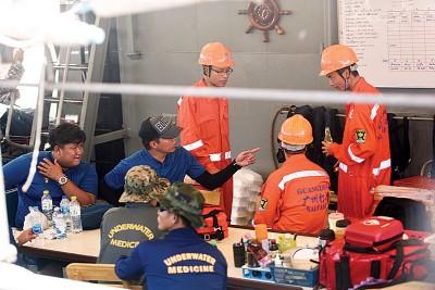 中国交通运输部广州打捞局救援队成员(橘色衣服)与泰方人员讨论搜救方案。(新华社照片)