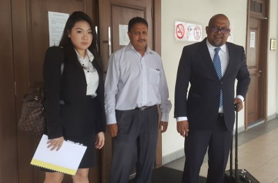 被告柏兰阿南(中间者)闻讯后与两名律师J.迪峇佐迪(右一)与黄栎烨(右一)步出法庭。