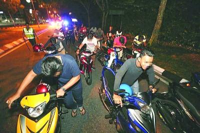 遭到检举的摩托骑士被警方训令各自推著摩托车步行2公里到交警执法组总部。
