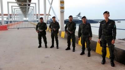 """普通行动队人员荷枪实弹站岗,看守""""平静号""""豪华游艇。"""