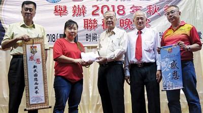 移交义卖本报筹获给两所独中的款项,左起陈初发、苏晓妹、李斯仁、李文强以及李坤泉。