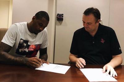 """""""甜瓜""""卡梅罗安东尼(左)在休斯顿火箭队总经理莫雷(右)面前签约。"""