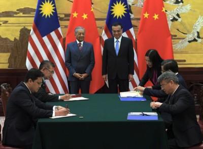 马哈迪(站者左)与李克强在人民大会堂见证马中双方代表签署谅解备忘录,作为强化吉隆坡和北京策略伙伴关系的标志。有关备忘录涉及农业和农业原 产品领域的合作。