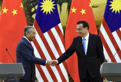 马哈迪(左)与李克强在召开联合记者会后握手,象征马中两国的关系更进一步。