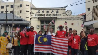 佳日星(左6)和雷尔(右5)在团队陪同下,一起到关丹律巴刹派送迷你国旗,共迎国庆。