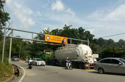 运输卡车驶入反方向道,企图硬闯限高杆。