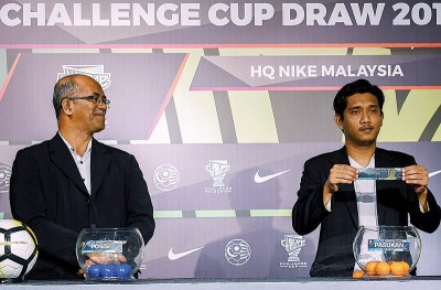 MFL理事慕斯塔扎(左)见证2018挑战杯标志设计获奖者费兹里为部分队伍抽签。