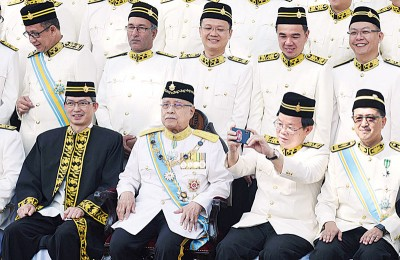 曹观友(前排左3)在等待拍摄大合照时,也顽皮地拿起手机欲拍摄前方一群的摄影记者。