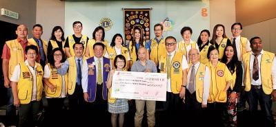 乔治市珍珠狮子会主席岑妙馨(前排左5)移交其中一张12万令吉模拟支票给cabet990亚洲城手机版父亲张吉祥。后排左3为谢柏梅。