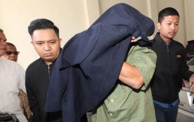 涉嫌滥用州务大臣特别拨款的国阵前任吉打州议员被反贪会押上亚罗士打法庭时,以大衣遮脸避开摄影镜头。