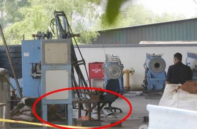 其中1名死者卧尸爆炸机器的下方(戏圈处)。