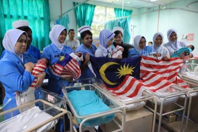 薛素娇(右4)及妇产科护士分别抱上国庆宝宝在病房开心合影。