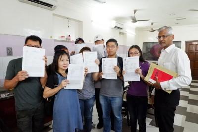 6名指遭替他们处理买卖合约的律师欺骗的受害者在达雅兰(右)的陪同下,向媒体出示其报案书。