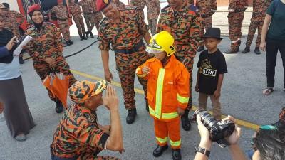 穿上消防员的救火衣,你就是我们一员!沙顿(左蹲者)教海卡举手致礼。