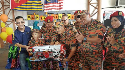 沙顿(左4)和大路后消拯局主任伊斯迈(左3)赠送一辆大型消防车玩具予海卡(左2),左1为其父亲诺斯任。