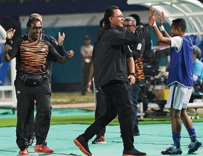 王金瑞(左)在大马亚运男足打败韩国队后,与队员击掌。