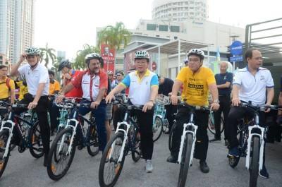 曹观友(中)在为共享车道主持推介礼后,也踩着脚踏车亲身体验由市政厅所设立的该车道