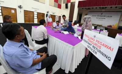 罗斯里(中)巡视无拉港补选提名中心,向选委会委任的工作人员汇报准备工作。