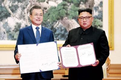 文在寅(左)以及金正恩(右)亮《平壤共宣言》。(法新社照片)