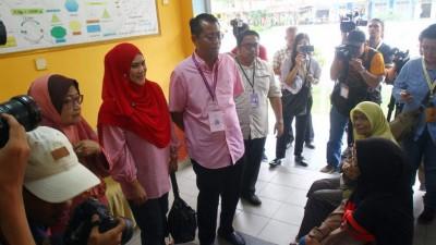 哈里米(右)与妻子苏海蒂到甘榜灵东岸国中巡视投票情况。