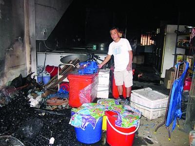 事主李文良检查被烧毁的储藏室。