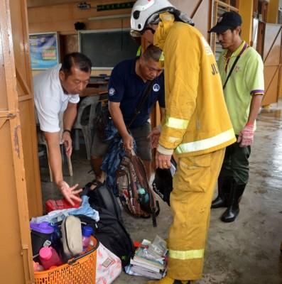 学员家长和义务消防队队员在于影响之课室协助搬运同学们的书包物件。