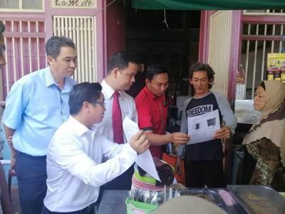 王宇航 (左)向居民派发通告,促请居民妥善处理垃圾源头分类。