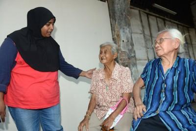 妮莎(左)安抚两名受惊的老妇许宝珍(中)及许秀华(右)。