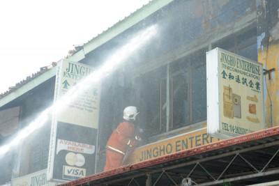其中一名消拯员在楼上进行灌水救火工作,以扑灭火势。