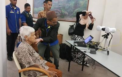 国民登记局流动登记队职员细心为老人梳理头发、调整角度,拍下新身份证照。