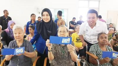 诺祖依花(后蓝衣)和黄顺祥(后站立者)与获得更新身份证老人一起开心合照。