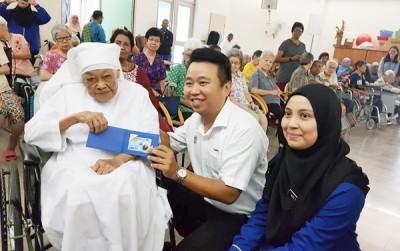 诺祖依花(右1)和黄顺祥(中)移交新身份证给最年长的阿斯丽修女。