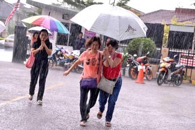 无拉港下起了滂沱大雨,选民们撑伞快步行走。